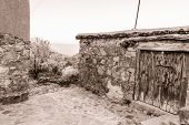 Fikardou village scene with blooming almond trees. The village located in Cyprus is a UNESCO heritage site, being a traditional mountain settlement preserving its 18th and 19th century physiognomy and architecture. Photo has been sepia toned poster