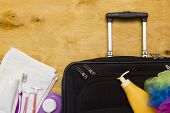 Suitcase traveler toiletries on a wooden background. poster