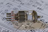 A vacuum tube lying on a circuit diagram. poster