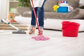 Close up of mop, worthy housewife with mop cleans floor in room poster