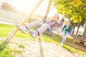 Young boy having fun on the swing. His mother or babysitter his swinging him and they are both enjoying it. Happy family and childhood lifestyle. poster