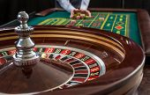 Roulette and piles of gambling chips on a green table in casino.  Man hand over casino chips  - bet. poster