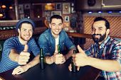 people, leisure, friendship, gesture and bachelor party concept - happy male friends drinking bottled beer and showing thumbs up at bar or pub poster