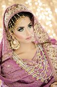 Portrait of a Beautiful Female Model in Traditional Indian Asian Bridal Wedding costume with makeup and jewellery poster