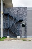 Fire escape staircase on the brick wall of a building poster