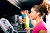 Running on treadmill in gym - group of women and men exercising to gain more fitness, the woman in front wears earplugs and enjoys music poster