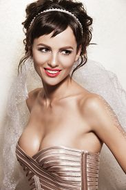 Portrait of affectionate brunette woman. Beautiful bride with wedding makeup hairdo and wedding decorations. Wedding ideas and bridal style.
