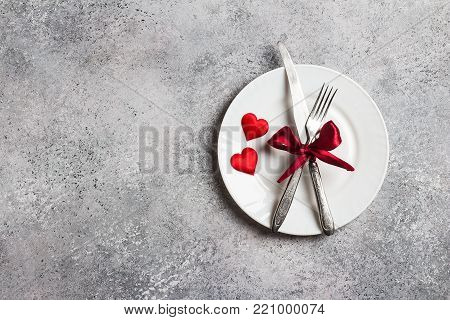 Valentines day table setting romantic dinner marry me wedding with plate fork knife on grey background with copyspace. Love gift woman making proposal romantic holiday wedding