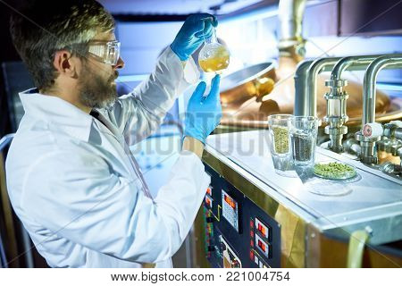 Confident inspector wearing white coat and protective goggles holding flask with beer in hands while checking its purity