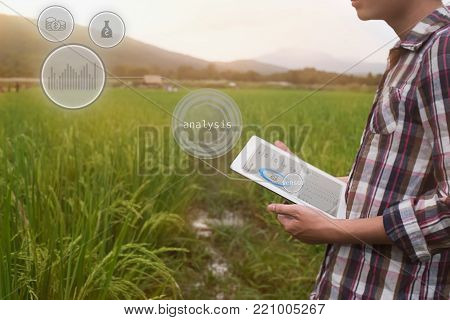 Agriculture farmer man hold tablet for analysis a report on rice agriculture Field with icon popup,agriculture technology concept.