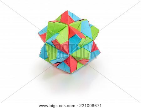 Geometric figure - dodecahedron, one of the species of polyhedra, made by method of modular origami with colored paper on a matte surface on a white background