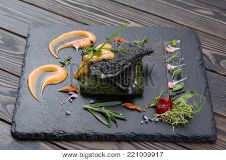Grouper's grilled fillet on a spinach bed. Fish on the black slate, shale board. Lemon pieces, sauce and rosemary. Piece of fish on wooden table