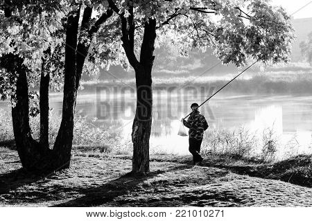 Autumn landscape in city park. Fisherman walking on path along foggy river. Trees on river bank. Black and white photo