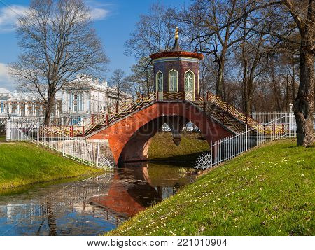 The Chinese-style bridge in the Alexander Park in Pushkin, St. Petersburg, against the backdrop of the palace in early spring in late April early May in clear sunny weather