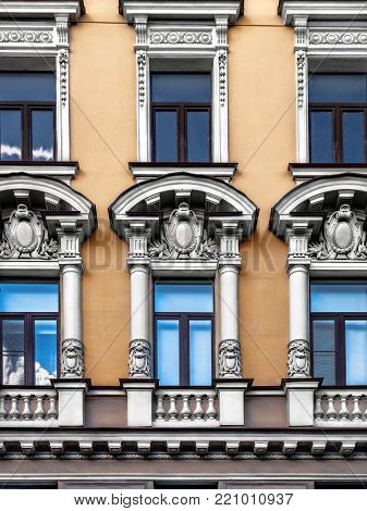 Architectural details balconies, pilasters, arches, rosettes, cornices, busts, white patterns on the facade of an ancient building in the center of St. Petersburg on the Griboedova Canal