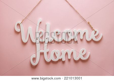 welcome home white wooden words on pink background