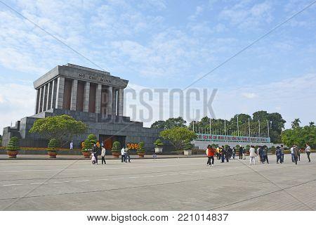 Hanoi, Vietnam - December 16th 2017. People walk past the Ho Chi Minh Mausoleum building in Ba Dình Square in Hanoi, Vietnam
