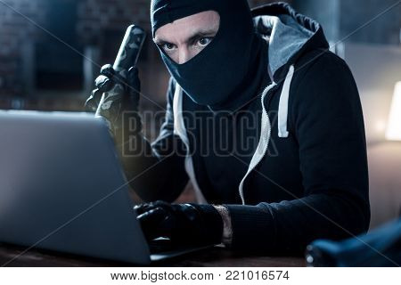 Stealing data. Skilful professional masked hacker sitting at the table and holding a torch and stealing date from the laptop at night