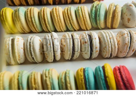 Set of different french cookies macaroons in a white boxCloseup. Coffee, chocolate, vanilla, lemon, raspberry, strawberry, pistachio, violet, rose, orange tastes macaroons.