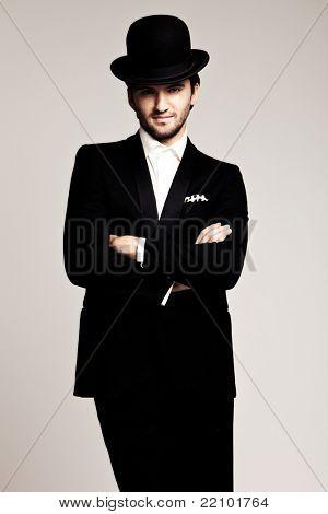 elegant young man in black tuxedo and derby,studio shot