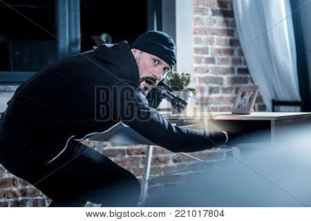 Being nervous. Nervous alarmed bearded burglar wearing black gloves and holding a torch while looking for documents in the table
