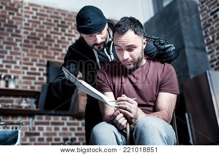Demands. Shocked frightened bearded man sitting with his hands tied while a killer standing near him and holding a gun and making the man sign a contract