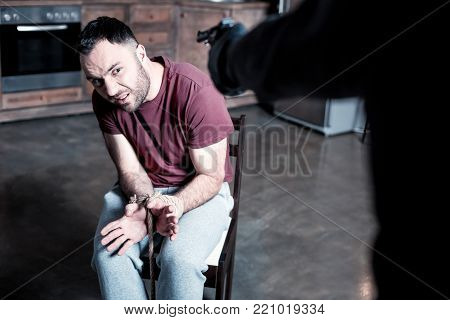 Do not kill. Shocked panic bearded man sitting with his hands tied while a killer standing near him and holding a gun