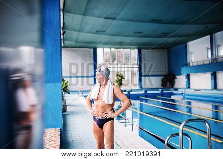 Senior man standing by the indoor swimming pool, arms on hips. Active pensioner enjoying sport.