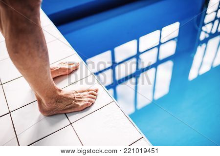 Legs of a man standing on the edge of the swimming pool. Unrecognizable man going to jump in the water