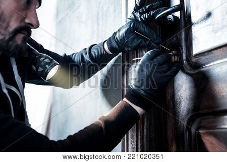 Unlocking the door. Concentrated professional bearded robber holding a torch and wearing gloves and unlocking the door poster