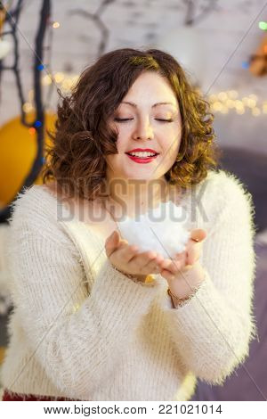 Fashionable Teenage Girl Wearing Holding Snowball In Studio In Front Of Christmas Tree