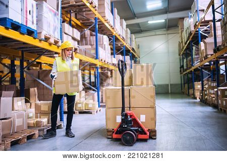 Young female warehouse worker loading up a pallet truck with boxes.