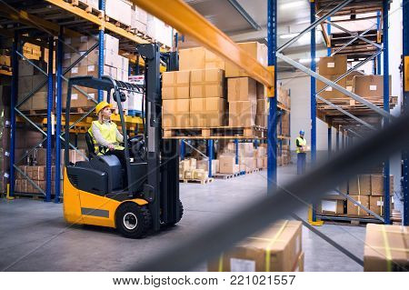Young workers working together. Woman forklift driver and a man in a warehouse.