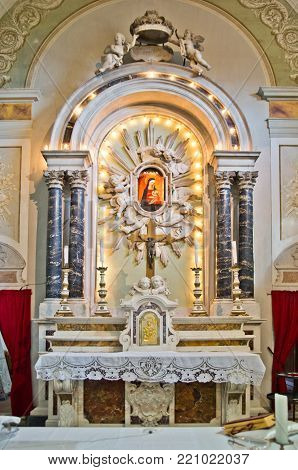 altar and tabernacle of an ancient neoclassical church with columns, cross and representation of the Madonna