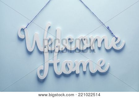 welcome home white wooden words on blue background