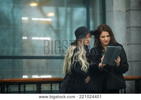 two beautiful young girls in warm clothes discussing work on a tablet on the street near the building