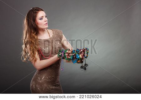 Pretty young woman holding hat and many plentiful of precious jewelry necklaces beads. Portrait of gorgeous fashion girl in studio on gray.
