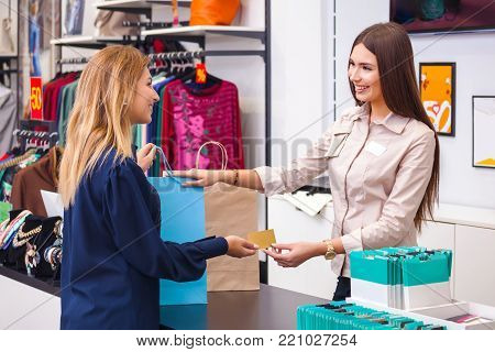 Young Woman With Shopping Bag Giving Her Credit Card To Seller In Clothing Shop