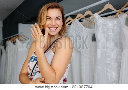 Female bridal store owner looking at wedding gown with a diary in hand. Dressmaker with diary examining bridal wear pattern.