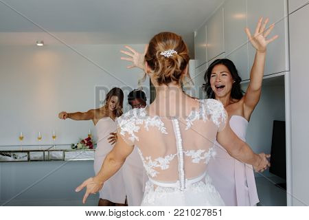 Female Bridal Store Owner Looking At Wedding Gown
