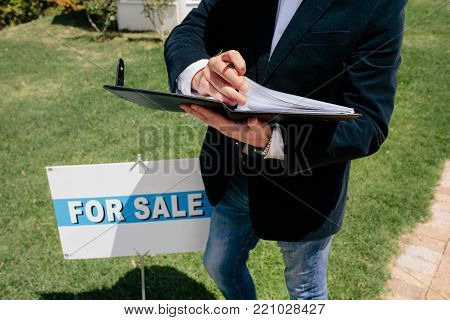 Male real estate broker standing outside with house documents file and for sale sign board. Cropped shot of realtor reviewing property paperwork.