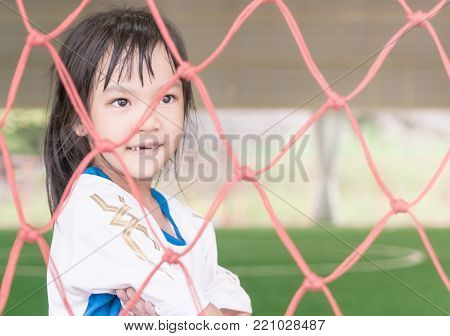 Soccer kid girl is stand inside a soccer goal on soccer training field