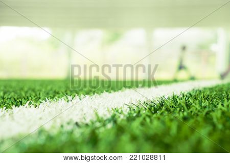 Soccer grass closed up shot with blue abstract on background