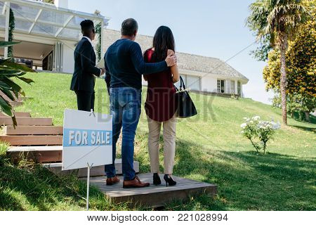 Real Estate Agent Standing By Signboard