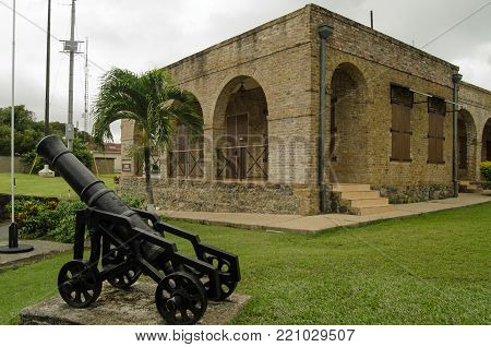 A cannon and the Officers Quarters, now a museum, at the histoic Fort King George in Scarborough, Tobago.