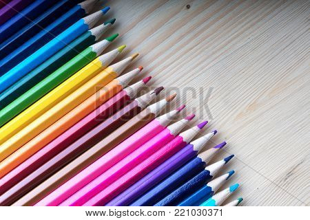 Multicolored pencils on wooden table, top view. Wooden crayons background with copyspace. School, sketching and drawing supplies.