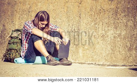 Man tourist backpacker relaxing outdoor sitting by grunge wall using tablet. Internet, tourism active lifestyle. Young hipster guy tramping poster