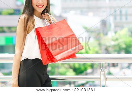 Beautiful young girl with red color shopping bags over the path way to the shopping mall. department store summer sale and fashion at center complex bangkok.