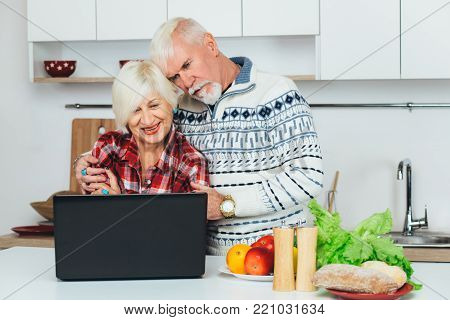 Elderly happy couple, cooking together, using laptop while standing in a white kitchen, at home. Cooking healthy eating for elderly people