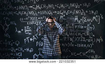 Young scientist man posing in chemical and mathematical equations wall room interior background